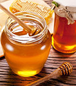 Wooden dripper in glass can full of honey on wooden table. — Stock Photo
