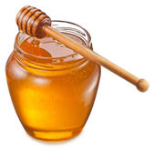 Glass can full of honey and wooden stick on it. Clipping paths. — Stock Photo