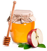 Glass can full of honey, piece of apples and wooden dipper. — Stock Photo