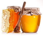 Glass cans full of honey, honeycombs and wooden stick. — Stock Photo
