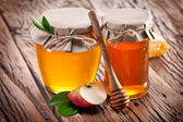 Glass cans full of honey and apple. — Stock Photo