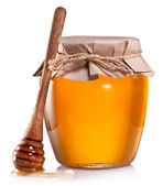 Glass can full of honey and wooden dripper on a white background — Stock Photo