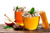 Glass cans full of honey, apples. honeycombs. Clipping paths. — Stock Photo