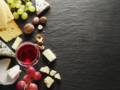 Different types of cheeses with wine glass and fruits. — Stockfoto