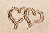 Hearts drawn on the beach sand. — Stock Photo