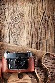 Old rangefinder camera on the old wooden table. — Stock Photo