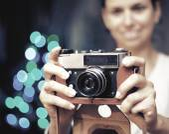 Smiling woman photographed retro camera. — Stockfoto