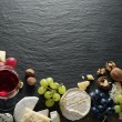 Different types of cheeses with wine glass and fruits. — Stock Photo #64632535