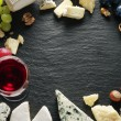 Different types of cheeses with wine glass and fruits. — Stock Photo #64632595