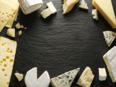 Different types of cheeses arranged as a frame on black board. — Stock Photo