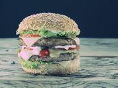 Hamburger on old wooden table. — Stock Photo
