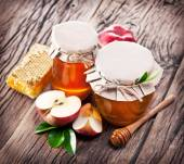 Glass cans full of honey, apples honeycombs on wood. — Stock Photo