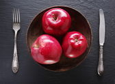 Red apples and table settings on a grey background. — Stockfoto