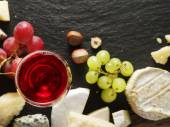 Different types of cheeses with wine glass and fruits. — Stock Photo