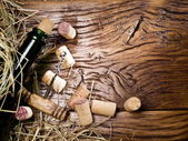 Wine bottle and corks on an old wooden table. — Stock Photo