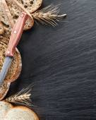 Bread slices, a wheat and a knife on the black stone desk. — Stock Photo