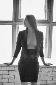 Sensual attractive brunette woman posing over the window — Stockfoto