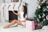 Fashion and sexy african woman decorating christmas treeм — Stock Photo