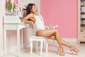 A sexy mulatto woman lying on the bed in a pink room — Stock Photo