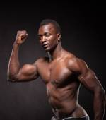 Beautiful and muscular black man in dark background — Stock Photo