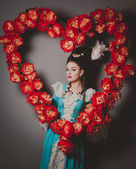 Old fashioned sexy woman with heart of flowers — Stock Photo