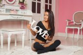 """A sexy mulatto woman in lingerie in a pink room with the words """"love"""" in the hands on pink room — Stock Photo"""