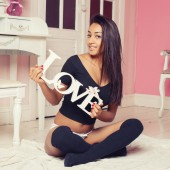 "A sexy mulatto woman in lingerie in a pink room with the words ""love"" in the hands on pink room — Stock Photo"
