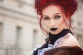 Sexy woman with gothic makeup and red hair and castle — Stock Photo
