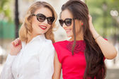 Two Beautiful youngs women with sunglasses walking in the city. Summer photo — Stock Photo