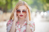 Beautiful  and fashion blonde young woman with sunglasses walking in the city. Summer photo — Stock Photo