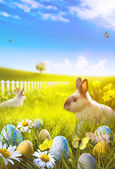 Art Easter bunny and easter eggs on field — Stock Photo