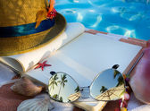 Art Straw hat , book and Sunglasses on the beach — Stock Photo