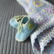 Hand knitted baby booties and blanket on the soft grey surface — Stock Photo #54650387