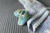 Hand knitted baby booties and blanket on the soft grey surface — Stock Photo