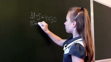 Schoolgirl writing mathematic expression — Stock Video