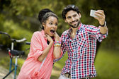 Young couple taking photo with mobile phone — Stock Photo