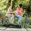 Young women riding on the tandem bicycle — Stock Photo #52780685
