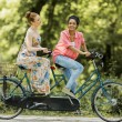 Young women riding on the tandem bicycle — Stock Photo #52780723
