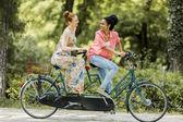 Young women riding on the tandem bicycle — Stock Photo