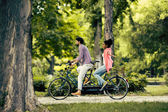 Young couple riding on the tandem bicycle — Stock Photo
