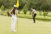 Young couple playing golf — Stock Photo
