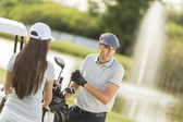 Young couple at golf court — Stock Photo