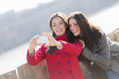 Happy young women taking photo with mobile phone — Stock Photo