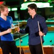 Young men playing pool and drinking beer — Stock Photo #72402511