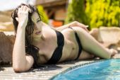 Young woman laying by the pool — Stock Photo