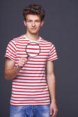 Man holding magnifying glass — Stock Photo