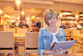 Woman sitting in the cafe using digital tablet — Fotografia Stock