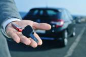 Man offering a car key to the observer — Stock Photo
