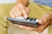 Young man using a calculator — Stock Photo