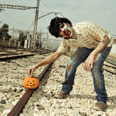 Zombie putting a carved pumpkin on the railroad tracks — Stockfoto